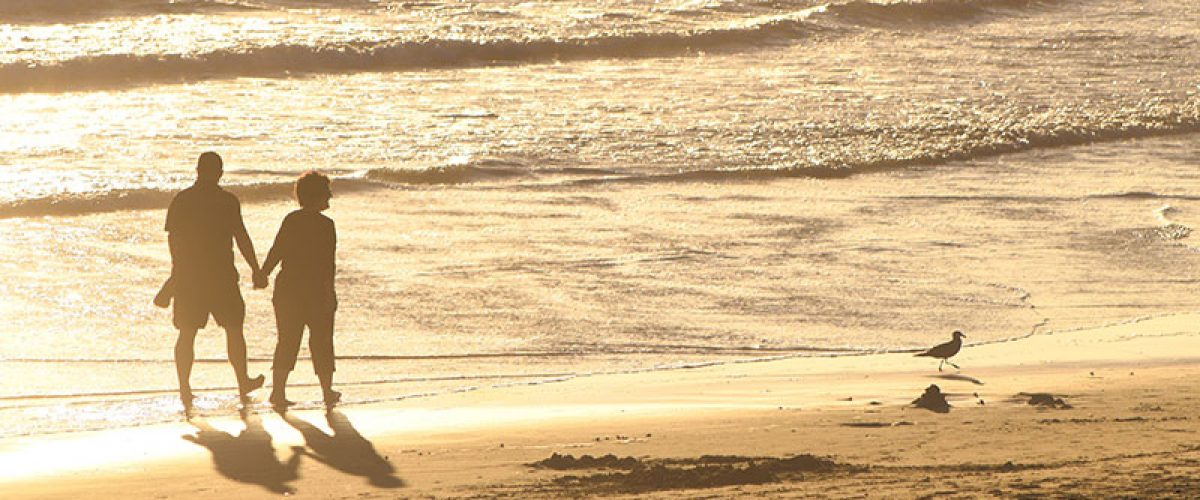 older-couple-holding-hands-and-walking-along-the-golden-beach-at-golden-hour-right-before-sunset_t20_4loEg_resize