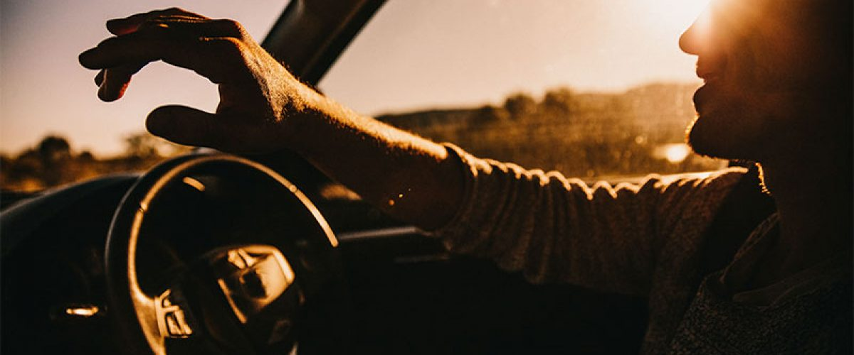 young-happy-male-adult-driving-car-at-sunset-smiling_t20_PQNN2_resize
